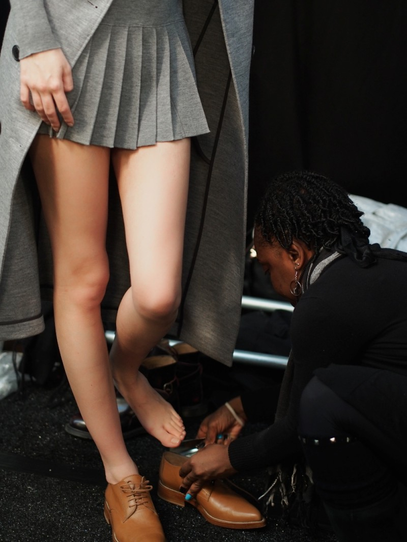 backstage at lacoste model getting dressed shoes