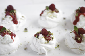 Pavlovas with rose whipped cream, raspberries and pistachios